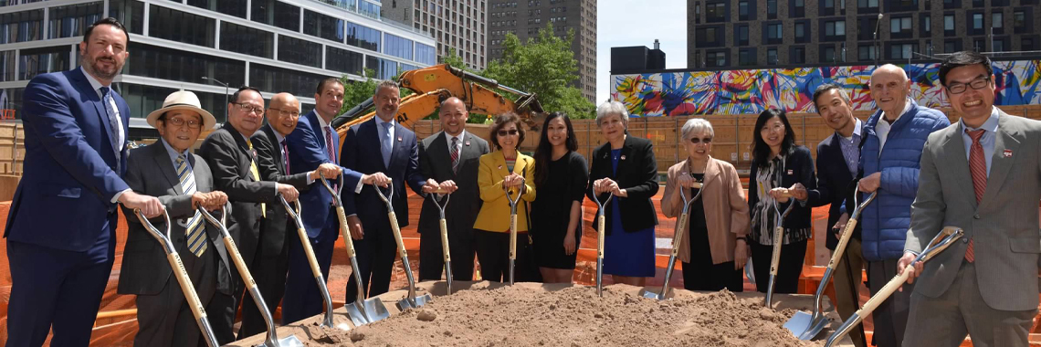 Board members smiling while holding shovels for a ground breaking event