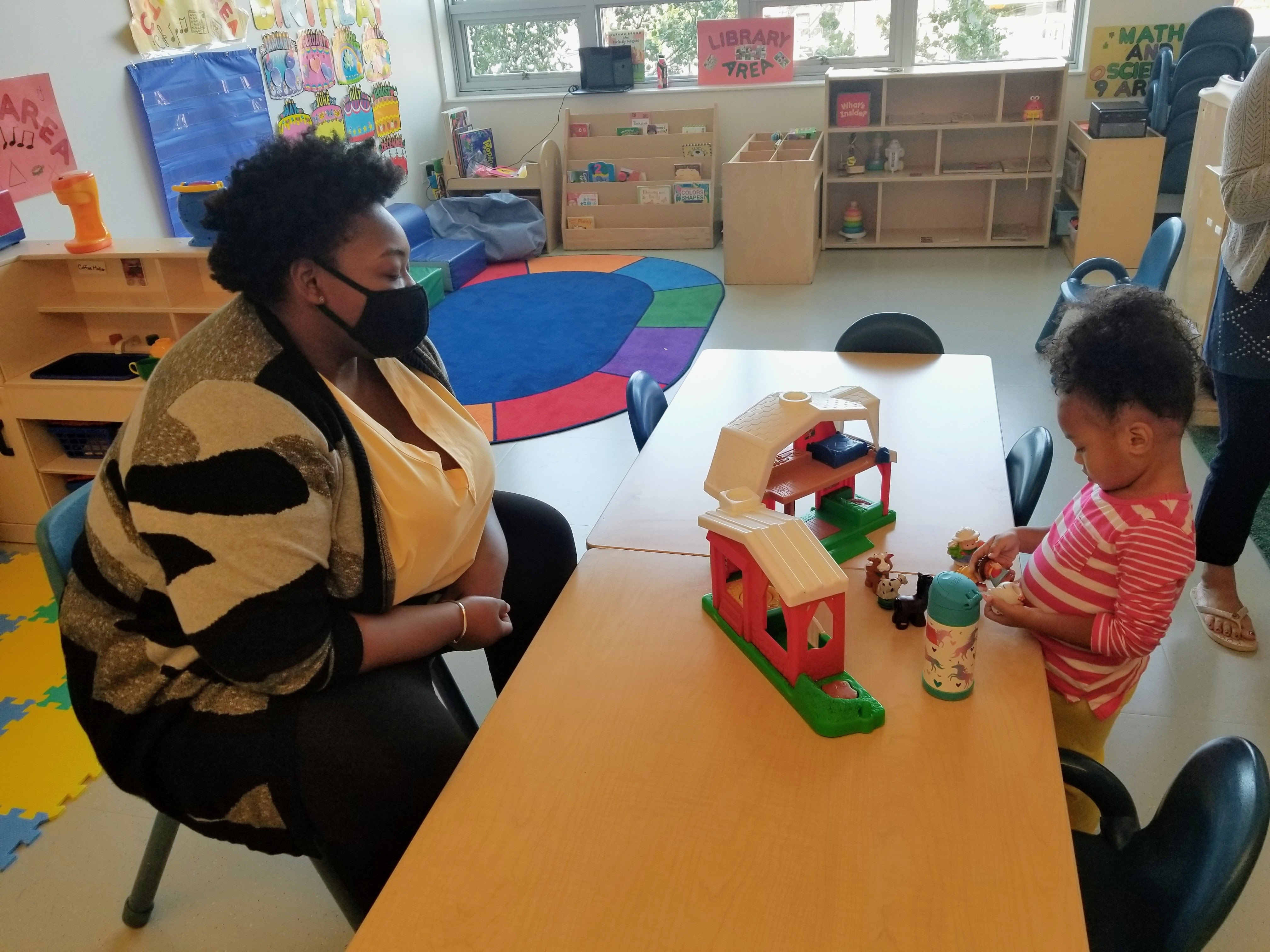 Staff wearing mask sit across a table from a child playing with blocks