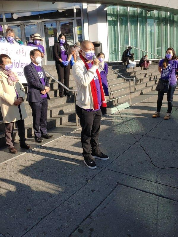 Mitch Wu speaks at the rally on the steps outside of the Flushing Library