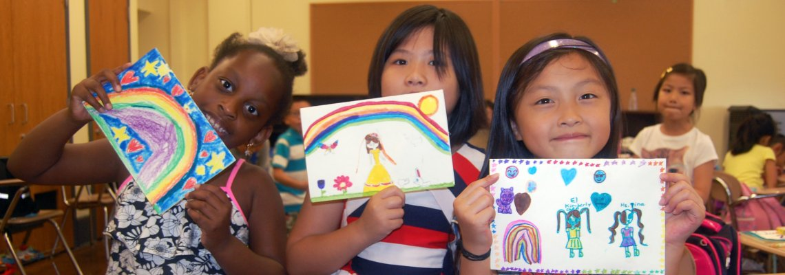 Three young girls showing their artwork