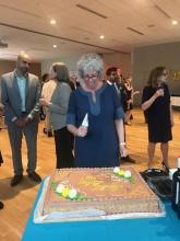 UNH Executive Director Susan Stamler Cutting the UNH Birthday Cake