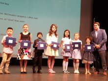 Anastasiia on stage with her certificate