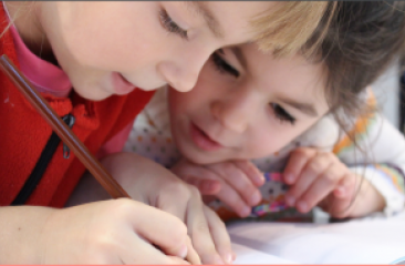 Two toddlers write sharing a pencil